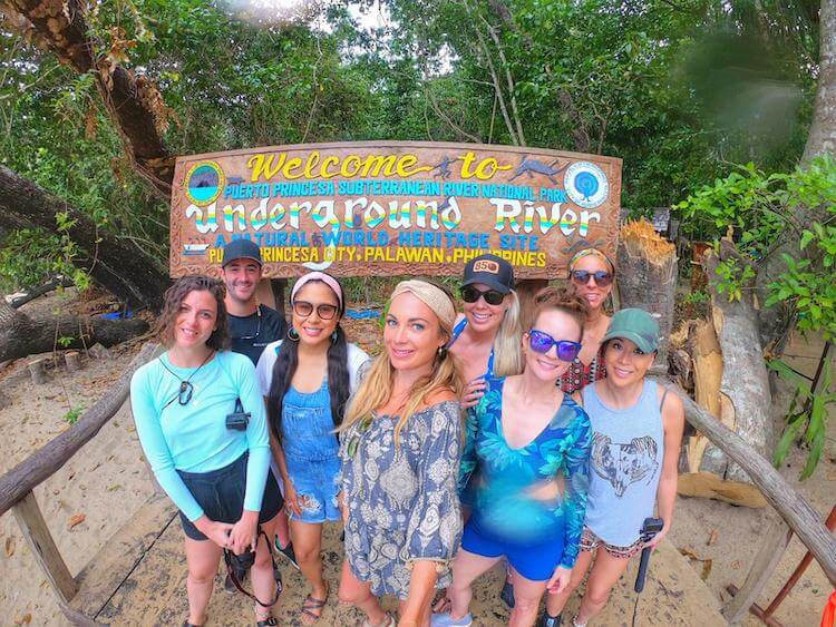 Philippines photo of group of travelers at Puerto Princesa underground river sign