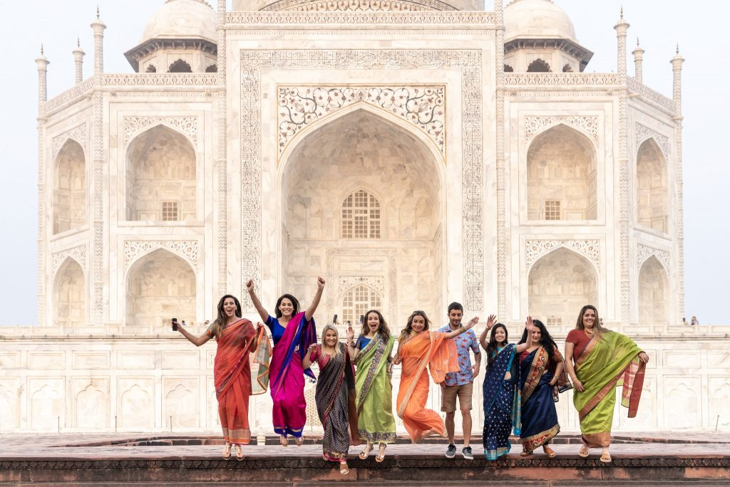 The travel group jumping together at the Taj Mahal
