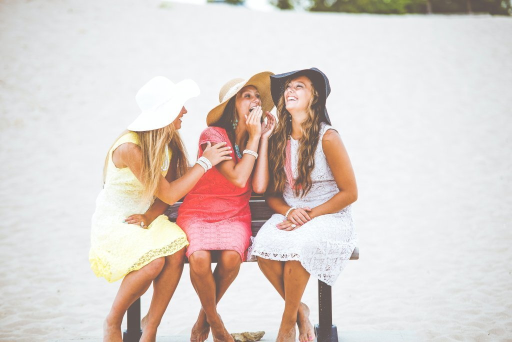 girls having fun laughing on a beach.